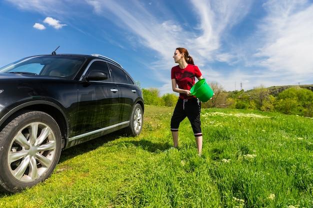 Mulher jovem lavando um veículo preto de luxo em um campo verde relvado em um dia ensolarado com céu azul, jogando um balde de água na lateral do carro