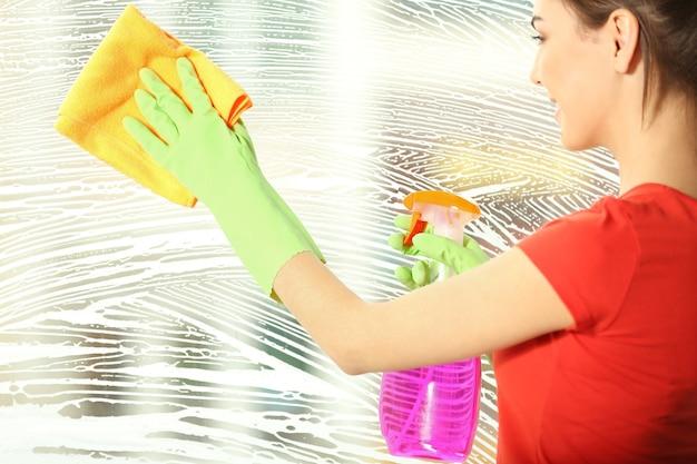 Mulher jovem lavando vidros de janela dentro de casa
