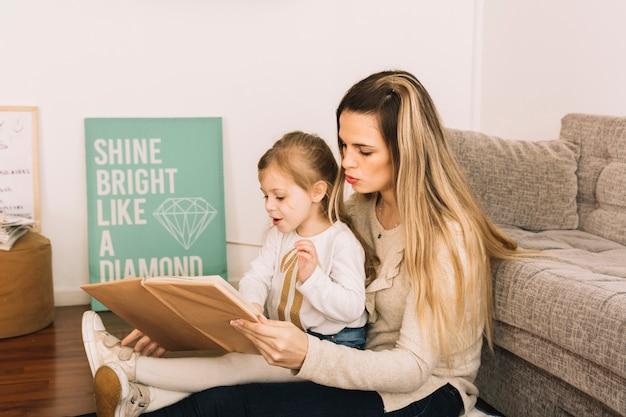 Mulher jovem, leitura, com, filha, ligado, chão
