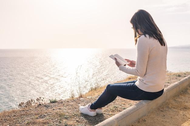 Mulher jovem, lendo um livro, frente, a, mar, em, primavera