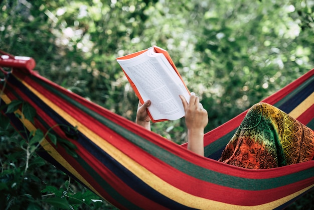 Mulher jovem, lendo um livro, mentindo, em, um, rede