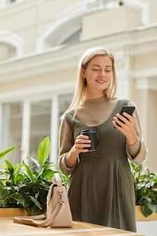 Mulher jovem lendo uma mensagem no celular enquanto bebia café em pé no shopping