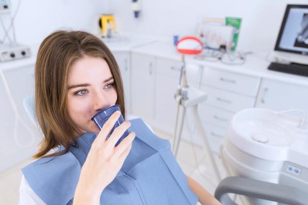 Mulher jovem, levando, água, enquanto, sentando, em, cadeira dental