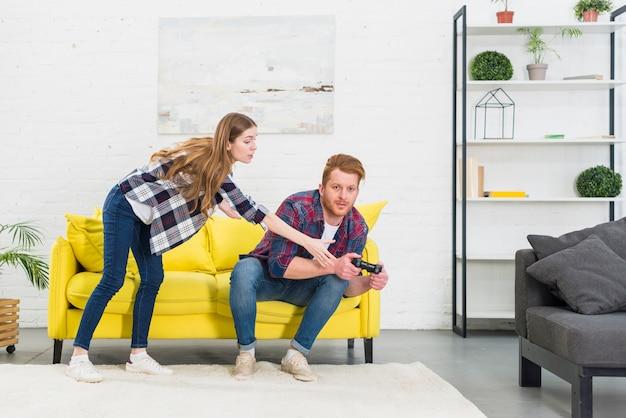 Mulher jovem, levando, joystick, de, seu, namorado, jogando videogame
