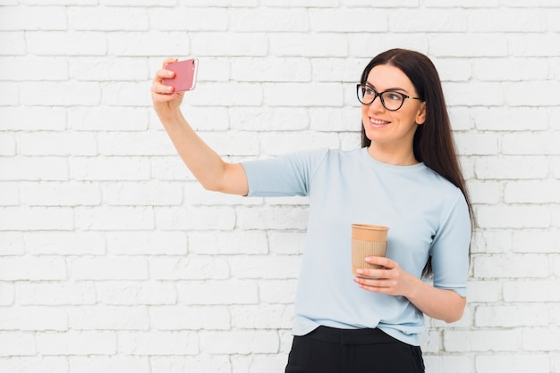 Mulher jovem, levando, selfie, com, xícara café