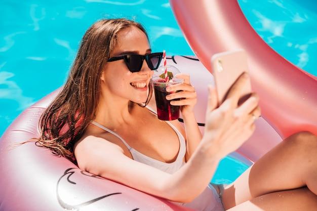 Mulher jovem, levando, um, selfie, em, nade anel