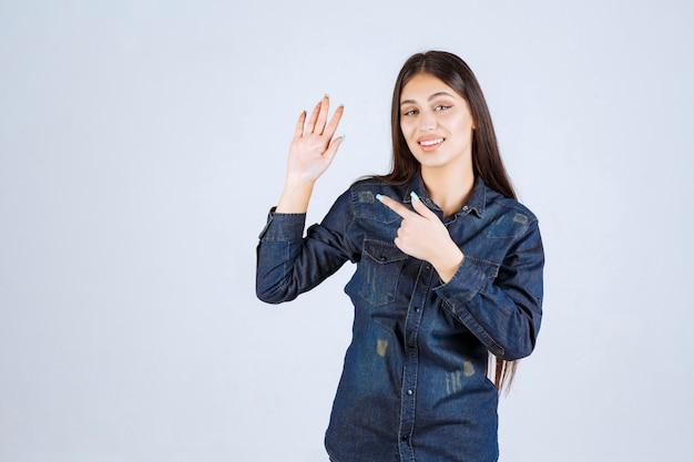 Mulher jovem levantando a mão para chamar a atenção