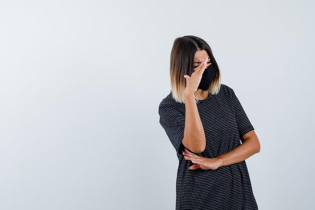 Mulher jovem, levantando a mão para esconder o rosto no vestido preto, máscara preta e parecendo envergonhado, vista frontal.