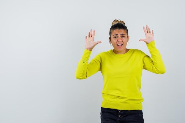 Mulher jovem levantando as mãos em posição de rendição, com suéter amarelo e calça preta