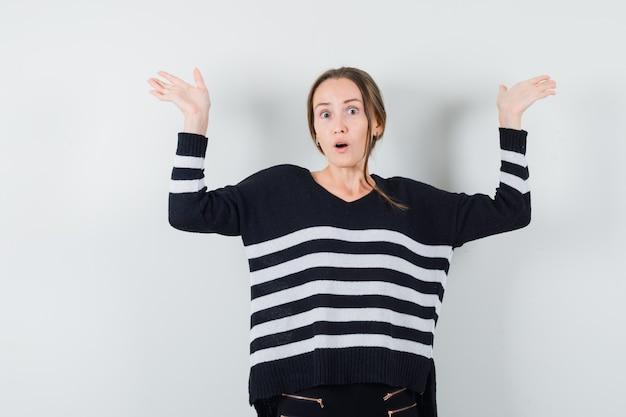 Mulher jovem levantando as mãos, mostrando um gesto de impotência em malha listrada e calça preta, parecendo surpresa