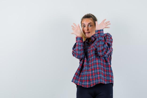 Mulher jovem levantando as mãos para parar com uma camisa xadrez e parecendo surpresa
