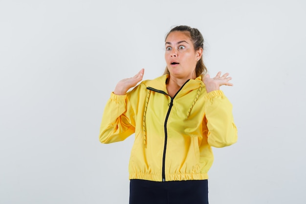 Mulher jovem levantando as mãos para se defender com uma capa de chuva amarela e parecendo assustada