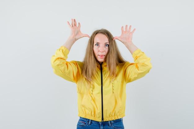 Mulher jovem levantando as mãos perto da cabeça e mostrando chifres de veado em uma jaqueta amarela e jeans azul