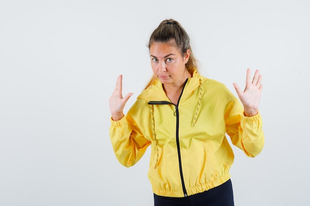 Mulher jovem levantando as mãos por rejeitar algo em uma capa de chuva amarela e parecendo segura
