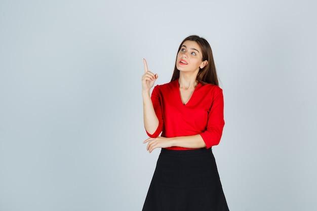 Mulher jovem levantando o dedo indicador num gesto de eureca na blusa vermelha