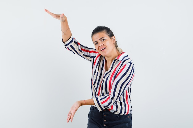 Mulher jovem levantando os braços, mostrando escamas em uma blusa listrada e parecendo otimista