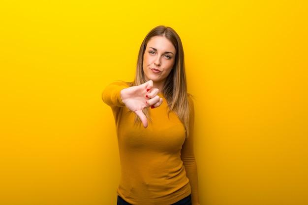 Mulher jovem, ligado, experiência amarela, mostrando, polegar baixo, sinal, com, expressão negativa