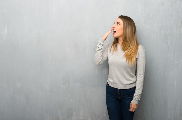 Mulher jovem, ligado, textured, parede, bocejar, e, cobertura, boca aberta, com, mão