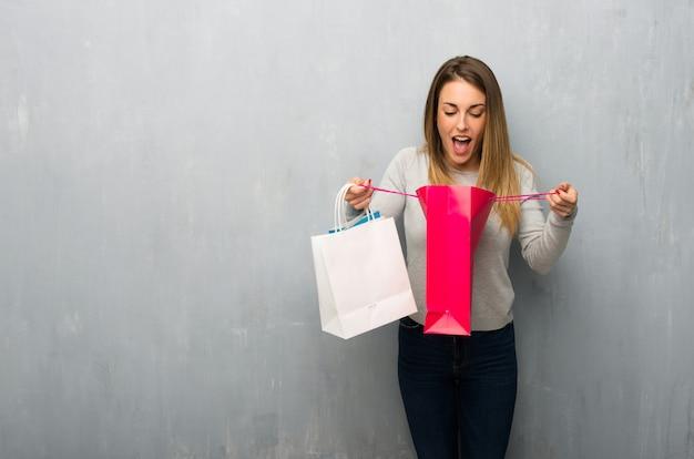 Mulher jovem, ligado, textured, parede, surpreendido, enquanto, segurando, um, muitos, bolsas para compras