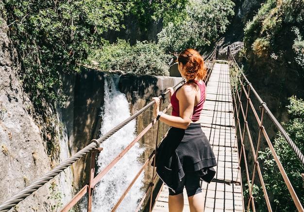 Mulher jovem, ligado, um, ponte suspensão, andar, ligado, a, los cahorros, rota, granada, espanha