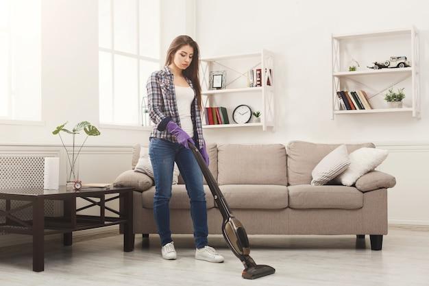 Mulher jovem limpando a casa com aspirador de pó