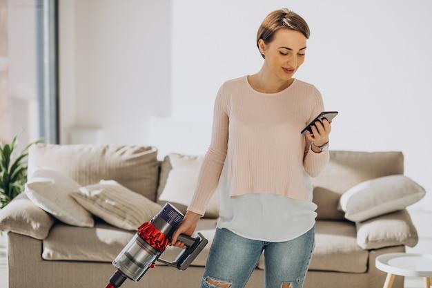 Mulher jovem limpando aspirador recarregável em casa