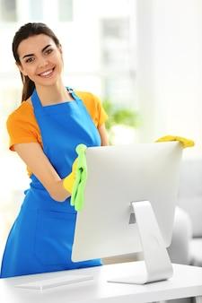 Mulher jovem limpando monitor de computador no escritório