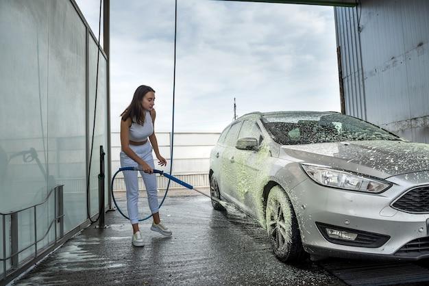 Mulher jovem limpando o carro dela com uma mangueira com espuma em spray e água sob pressão na lavagem manual da sujeira do carro