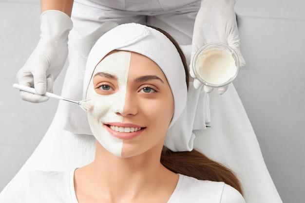 Mulher jovem limpando o rosto em esteticista profissional