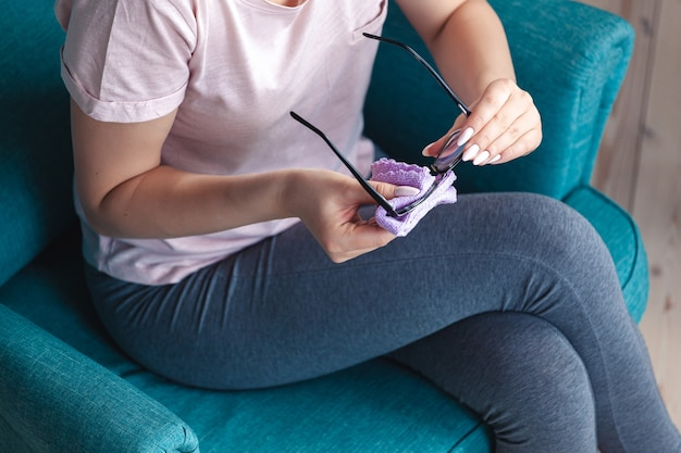 Mulher jovem limpando óculos com um guardanapo enquanto está sentada em um ch