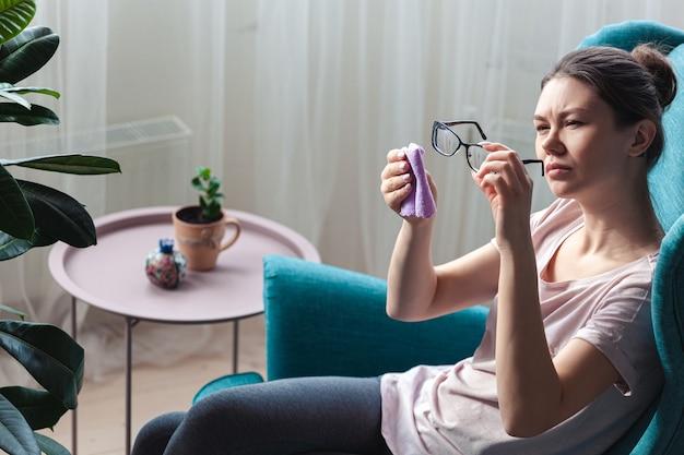 Mulher jovem limpando óculos com um guardanapo enquanto está sentada em uma cadeira