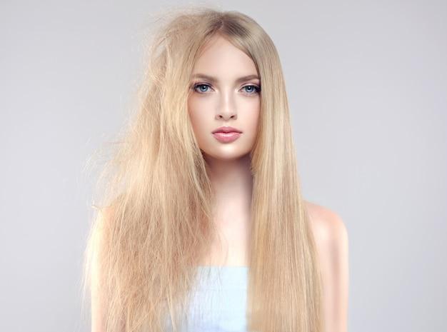Mulher jovem, loira, com cabelos lisos e brilhantes de um lado e cabelos emaranhados em más condições do outro lado.