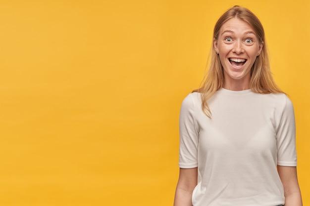 Mulher jovem loira espantada e feliz com sardas na camiseta branca parece surpresa e olhando para a câmera sobre a parede amarela