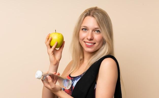 Mulher jovem loira esporte com uma maçã e uma garrafa de água