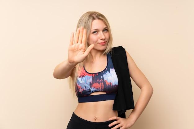 Mulher jovem loira esporte sobre parede isolada, fazendo o gesto de parada com a mão