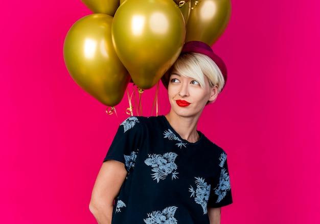Mulher jovem loira feliz e festeira com um chapéu de festa em pé na frente de balões, olhando para o lado isolado na parede rosa com espaço de cópia