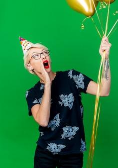 Mulher jovem loira festeira usando óculos e boné de aniversário segurando e olhando para balões, mantendo a mão perto da boca chamando isolado na parede verde