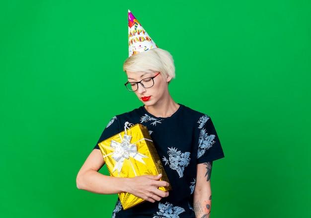 Mulher jovem loira festeira usando óculos e boné de aniversário segurando e olhando para uma caixa de presente isolada na parede verde com espaço de cópia