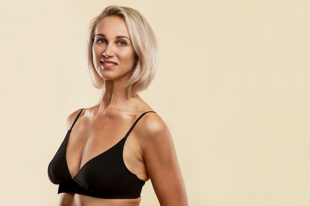 Mulher jovem loira sorridente no top preto de esportes.