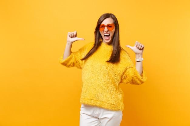 Mulher jovem louca engraçada de suéter de pele e óculos coração laranja gritando apontando polegares sobre si mesma isolada em fundo amarelo brilhante. emoções sinceras de pessoas, conceito de estilo de vida. área de publicidade.
