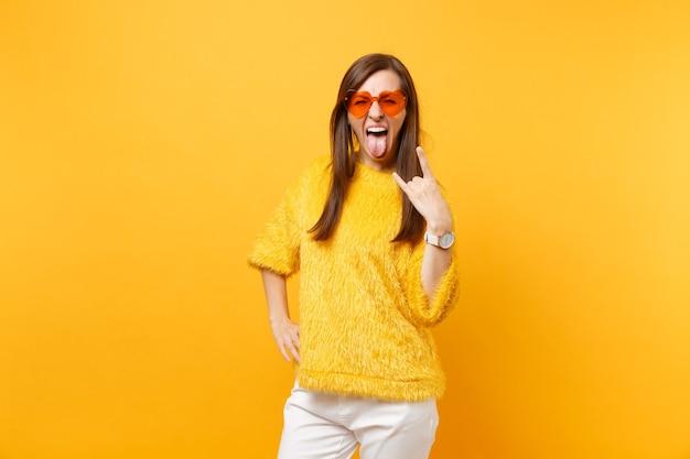 Mulher jovem louca engraçada de suéter de pele e óculos coração laranja gritando, mostrando sinal de rock-n-roll isolado em fundo amarelo brilhante. emoções sinceras de pessoas, conceito de estilo de vida. área de publicidade.