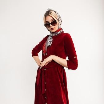 Mulher jovem luxuosa em elegantes óculos de sol em lindo lenço de leopardo na cabeça em vestido de moda cor de vinho se passando perto de uma parede branca vintage. garota loira atraente negócios dentro de casa. senhora sexy.