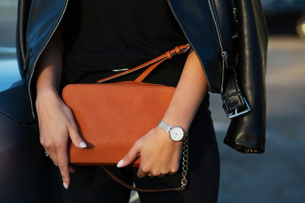 Mulher jovem luxuosa na jaqueta de couro preta, segurando a bolsa laranja. foto de close