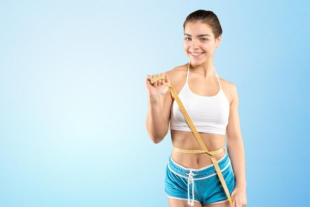Mulher jovem magro com uma fita métrica