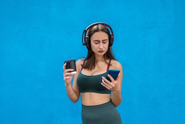 Mulher jovem magro em fones de ouvido com um copo de bebida e ouvindo música com o telefone após o exercício isolado sobre fundo azul