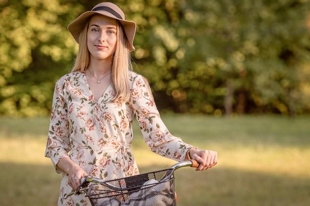 Mulher jovem, magro, loira de bicicleta contra a paisagem desfocada do parque. tom de cor de outono.