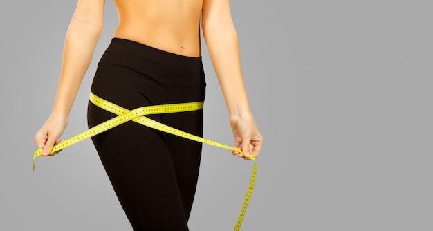 Mulher jovem magro, medindo a cintura dela