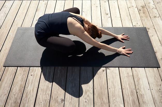 Mulher jovem magro meditando, relaxando e praticando ioga no cais de madeira perto do lago.