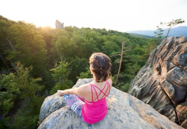 Mulher jovem magro turista sentado em cima de uma rocha enorme fazendo yoga