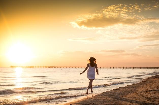 Mulher jovem magro vestido branco correndo na praia ao pôr do sol de verão